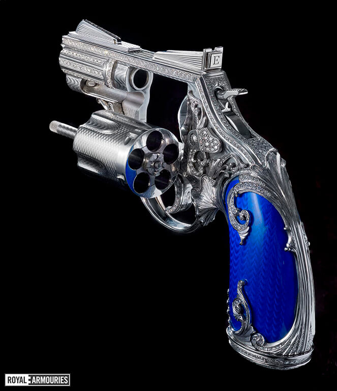 rear view of a highly decorated revolver with blue grips and encrusted with diamonds shown with cylinder open
