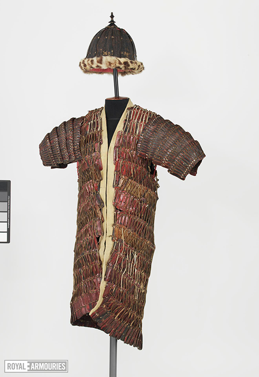 Mounted lamellar coat and a helmet. The coat is full length, and the leather is lacquered red and gold. The helmet is hemisperical and lined with leopard skin