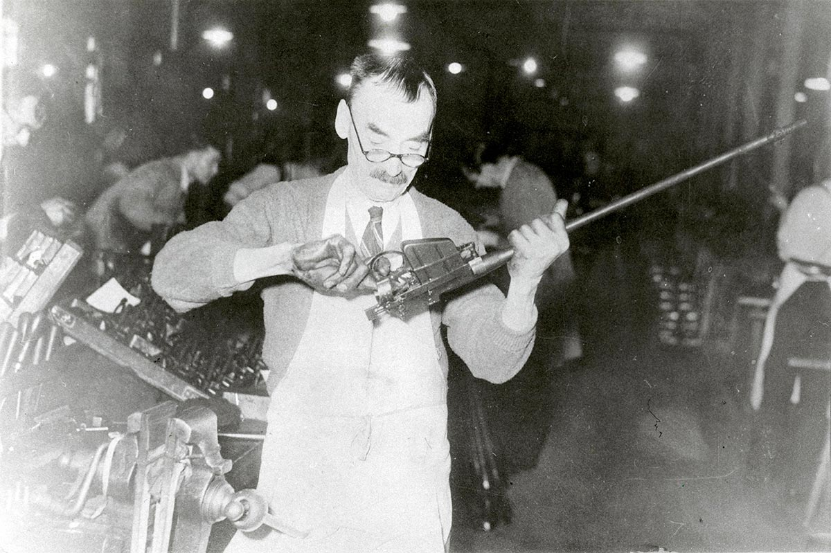 Middle-aged man in a factory wearing glasses inspecting the trigger assembly of a rifle