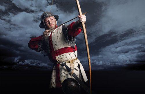 An medieval english longbowman prepares to loose an arrow