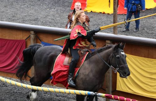 Woman on horseback jousting for the ring