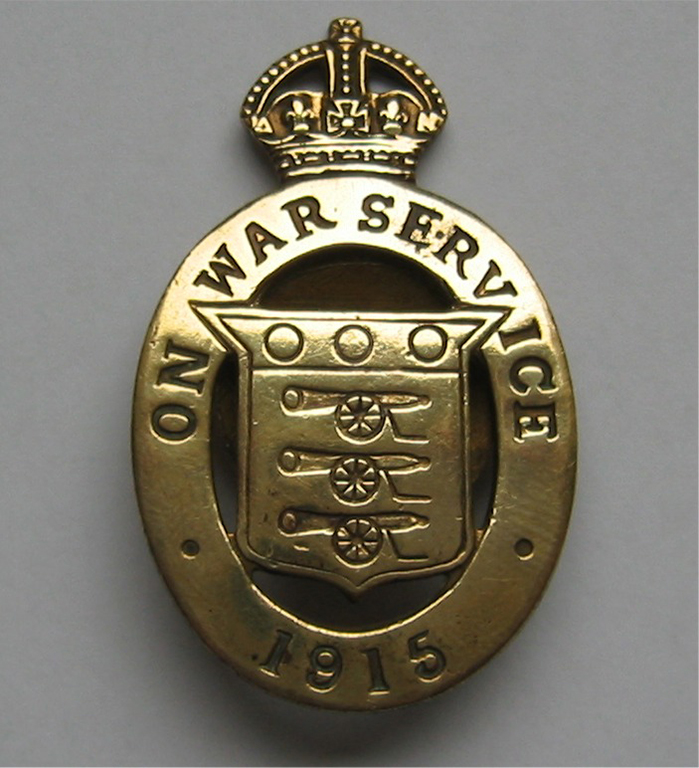 "Brass badge featuring 3 cannons and 3 balls, surmounted by a crown and the motto ""on war service 1915"""
