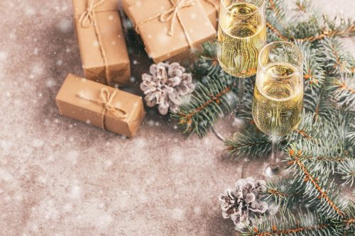 Flutes of sparkling champagne and gifts nestle amongst the snow dusted christmas tree branches and pine cones