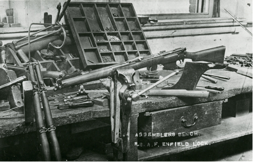 Rifle held in a bench vice surrounded by tools and parts