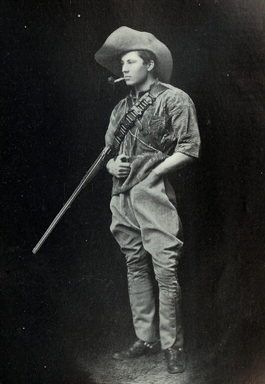 ewart scott grogan dressed in a floppy hat and carrying a rifle with a pipe in his mouth