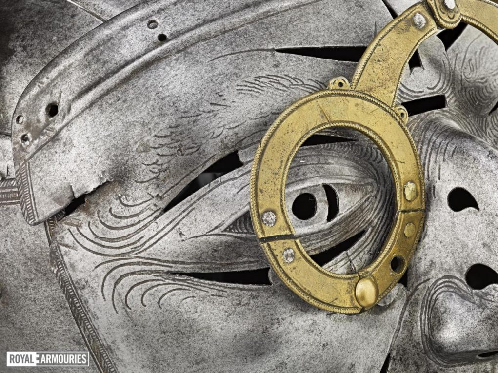 close up of the face of the mask, showing the brass spectacle frames and intricate silver etching around the eyes.
