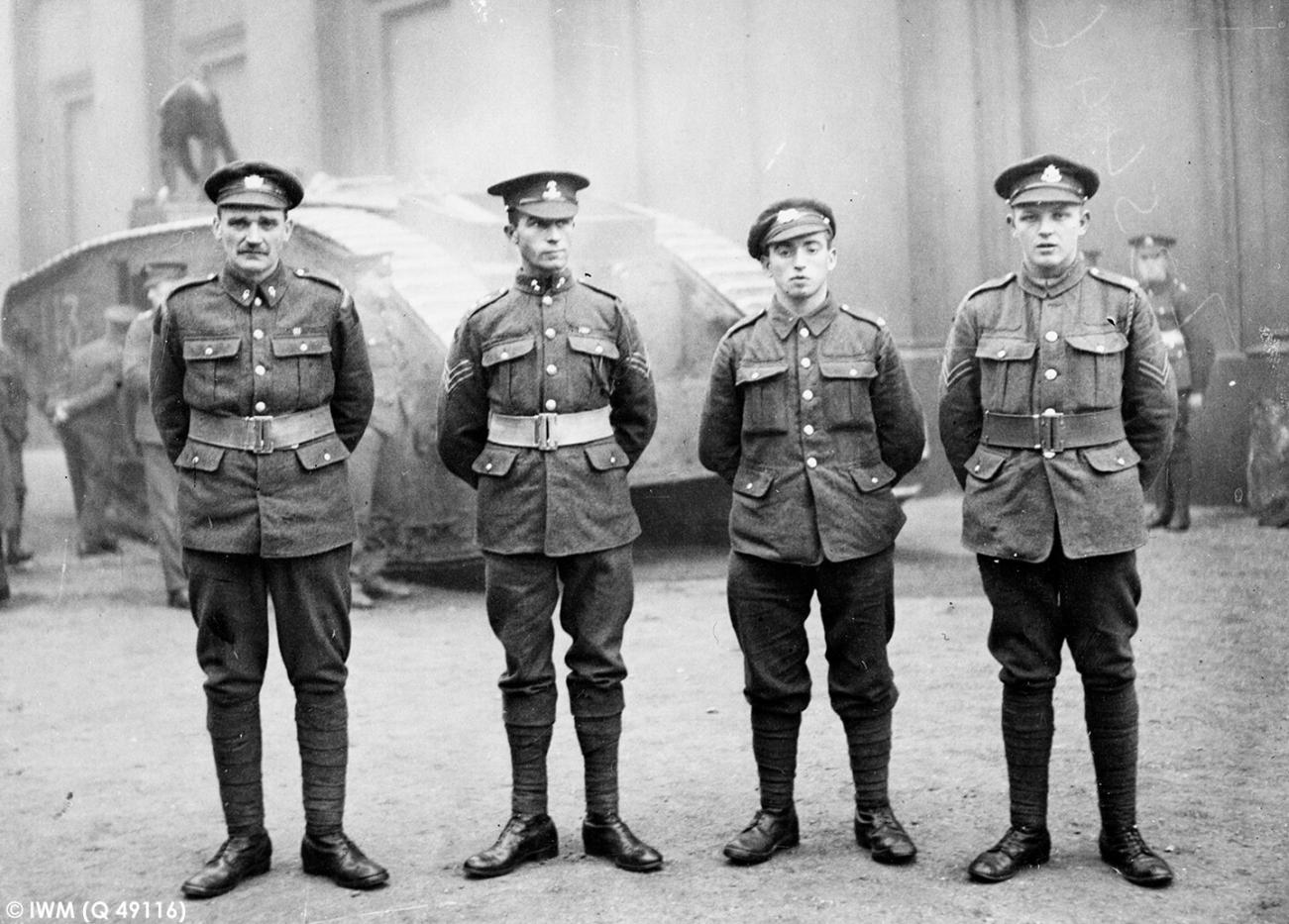 Four First World War soldiers stood at ease in a line, with a Churchill tank in the background