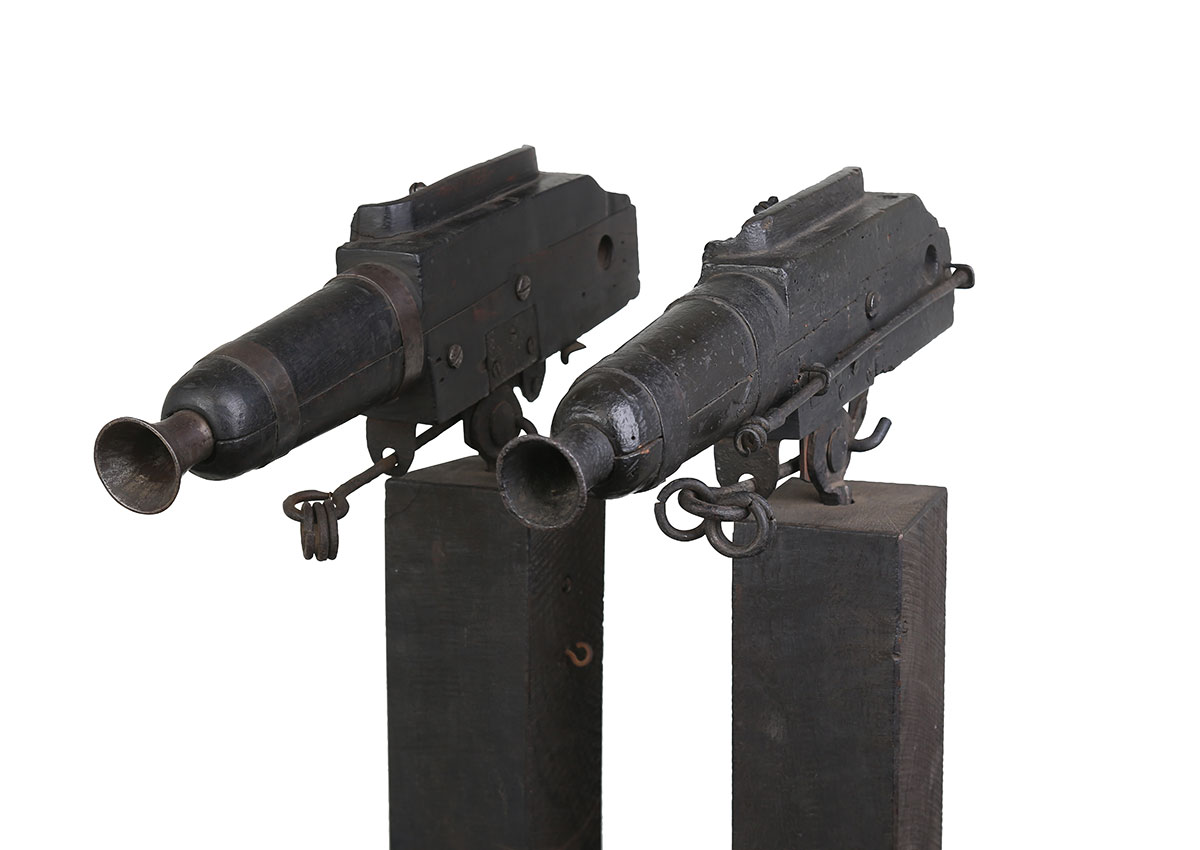 two spring guns side by side