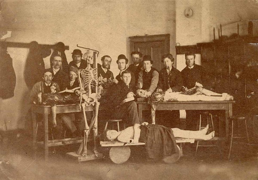 students posing in a classroom next to three cadavers and a skeleton