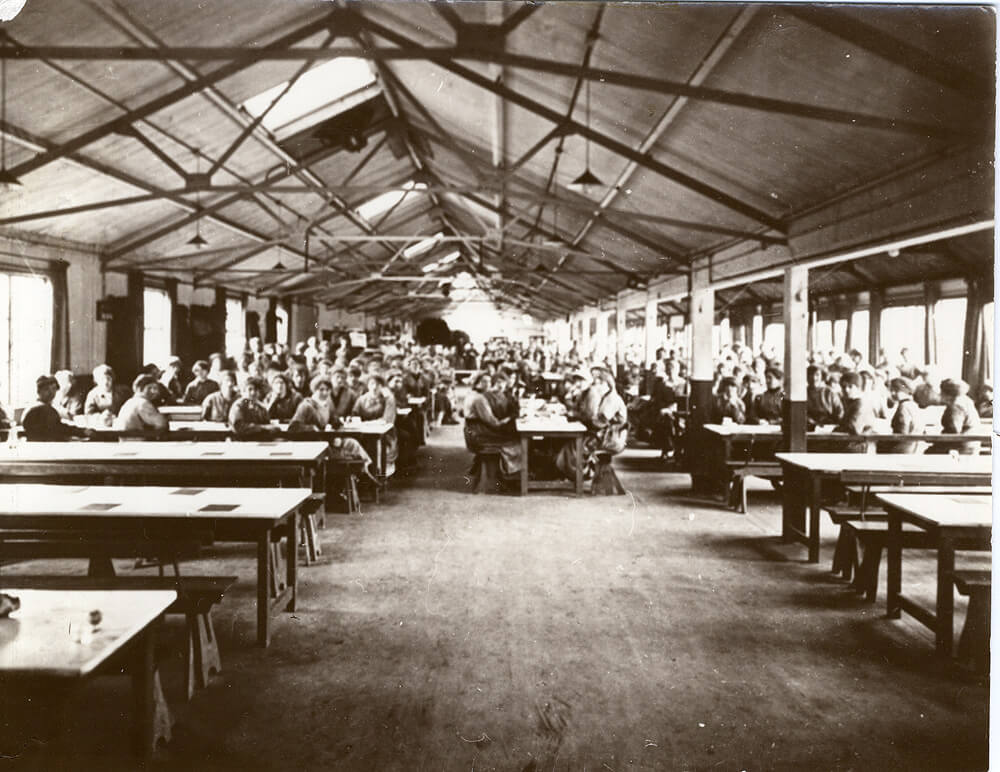 hundreds of women sat in the canteen at wooden tables and benches