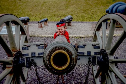 A small boy in redcoat uniform takes aim behind a cannon