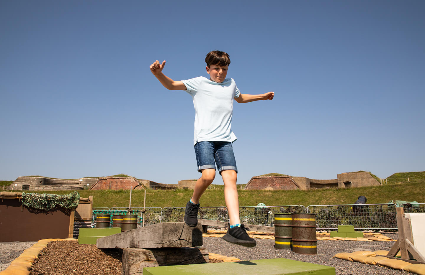 A boy leaping over an assault course