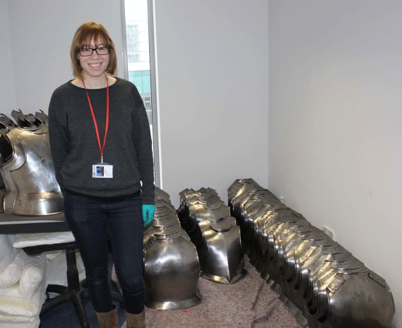 conservator standing next to a row of Toiras breastplates and backplates
