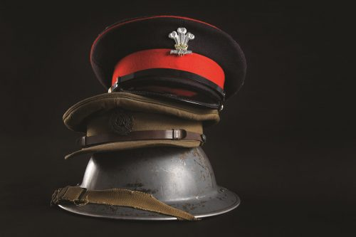 a pile of army caps on a steel helmet