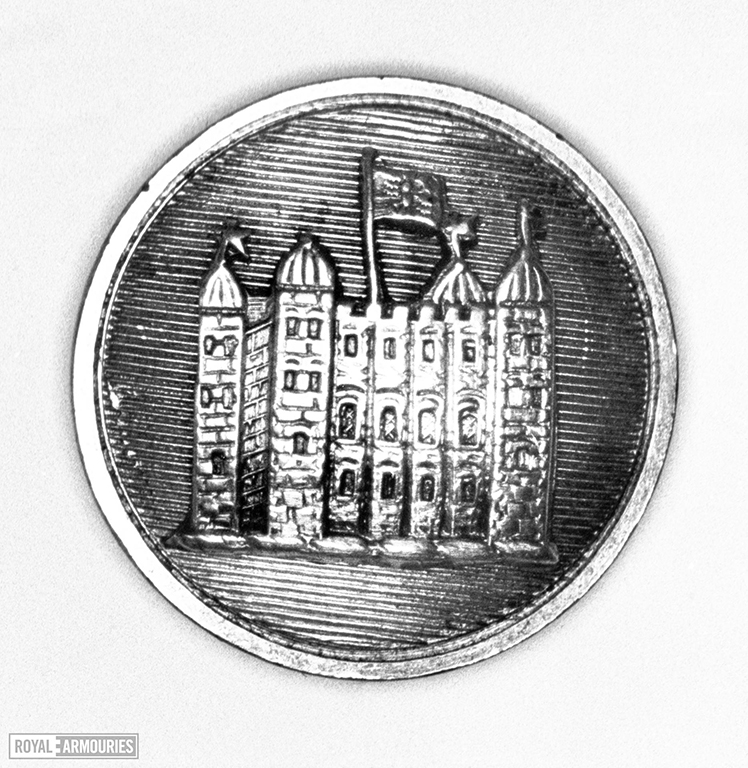 Button with the white tower at tower of london embossed on it