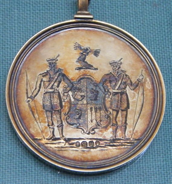 A round archery medal embossed with the coat of arms of the Stockwell Archers, flanked by two uniformed archers, the arms surmounted by an arm grasping five arrows