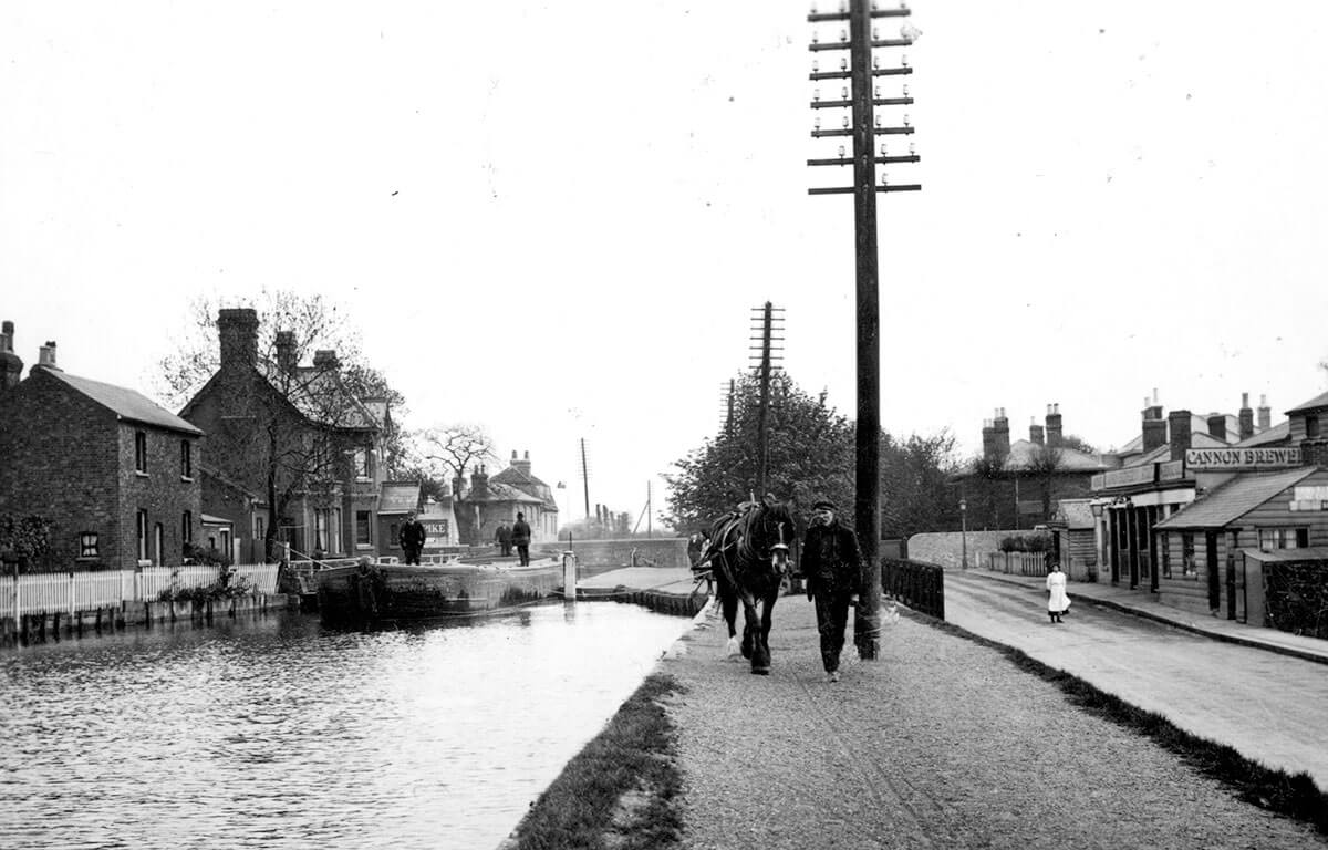 man walking a horse along a canal with pubs in the background