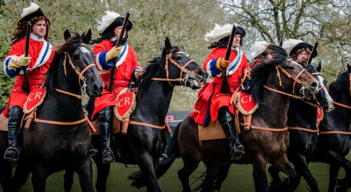 five cavaliers in red coasts charging on horseback