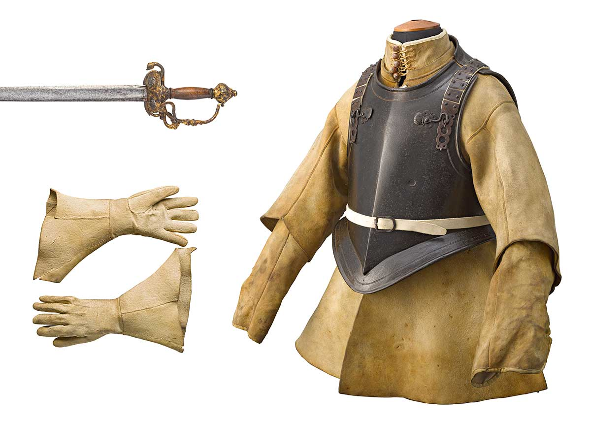 A 17th century armour: leather coat with stell breast and back plates, gloves and sword.