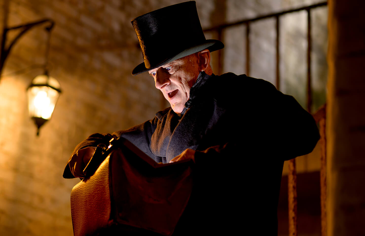Creepy victorian man in top hat staring malevolently into a doctor's bag