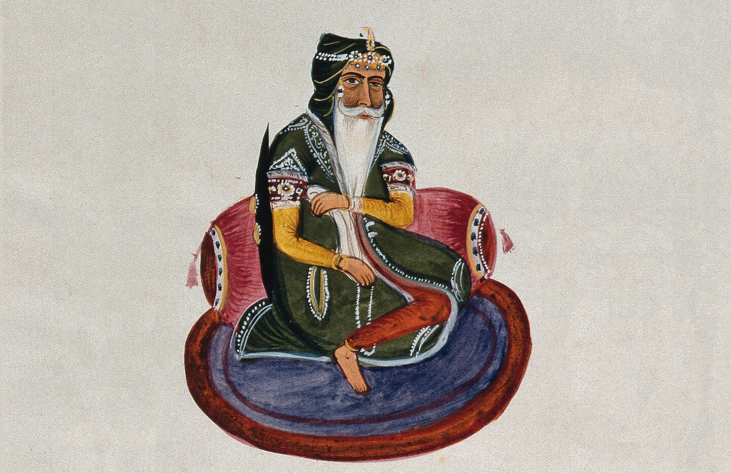 An indian ruler sits crossed legged