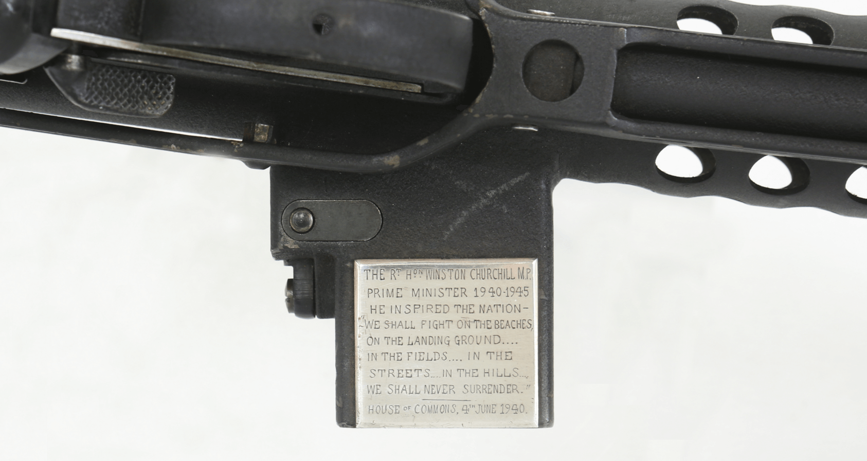A close up of a machine gun with a silver plaque with churchills speech
