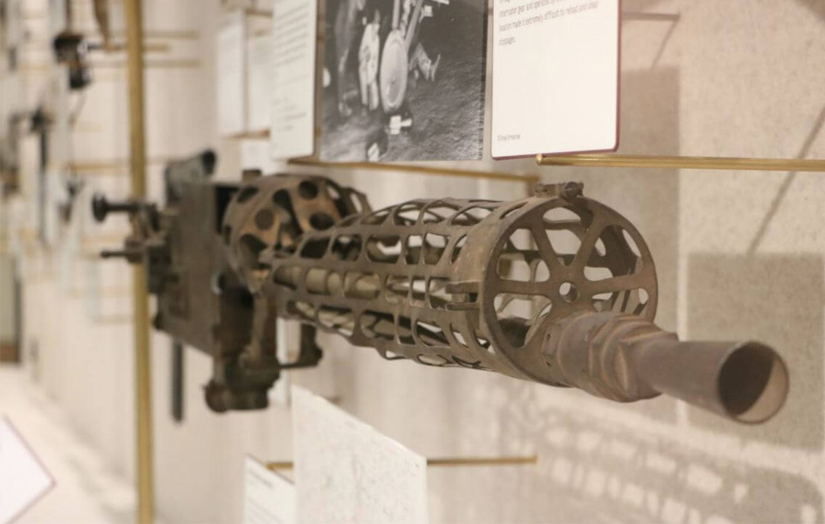 A mounted Machine gun pointed towards the viewer. It is rusted from age and bent from battle damage.
