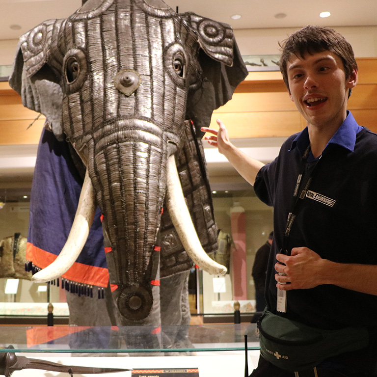 museum assistant in front of the elephant Armour