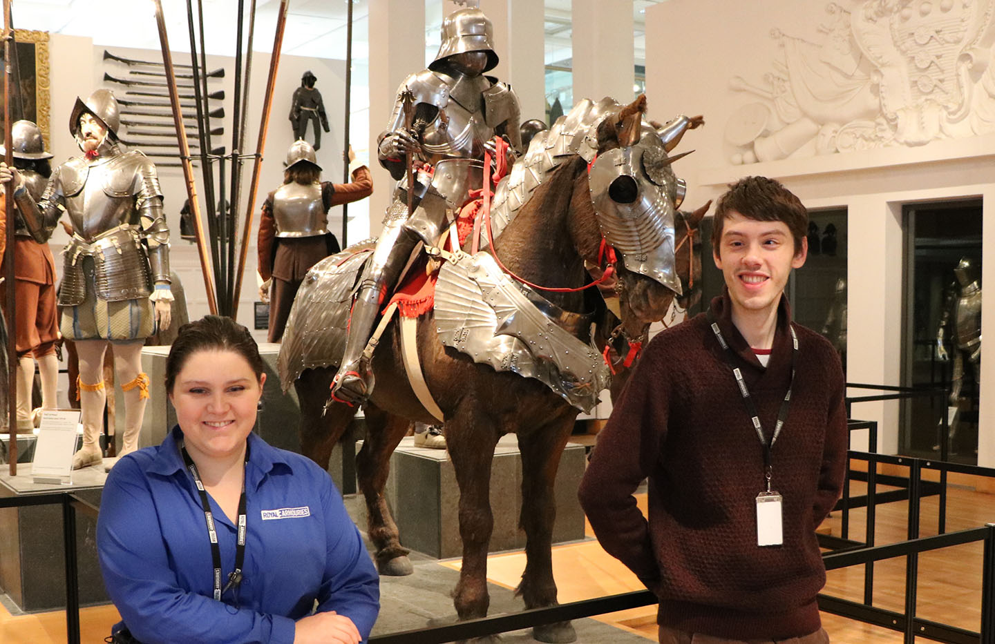 Museum assistants Tom and Brittany stand in from of an armored horse and knight display