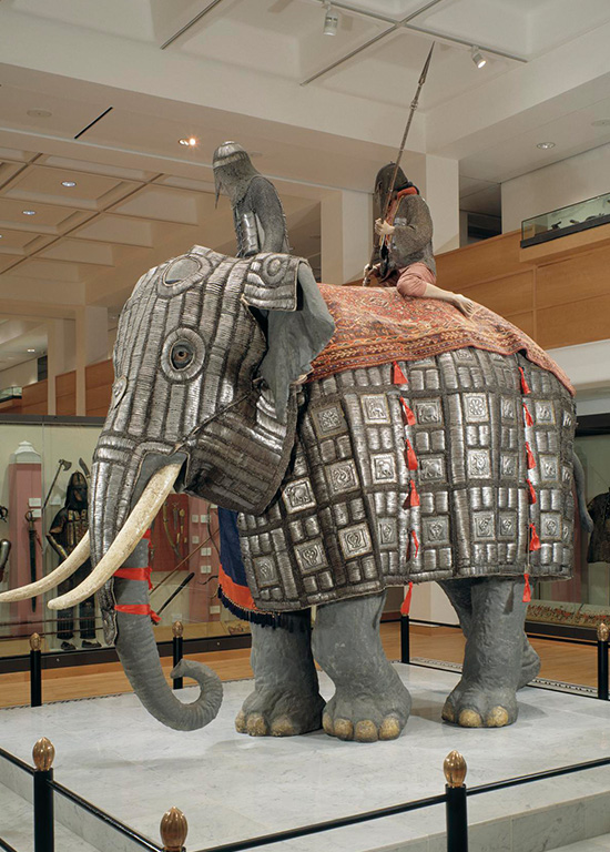 Two riders ride an armored elephant in a museum duisplay