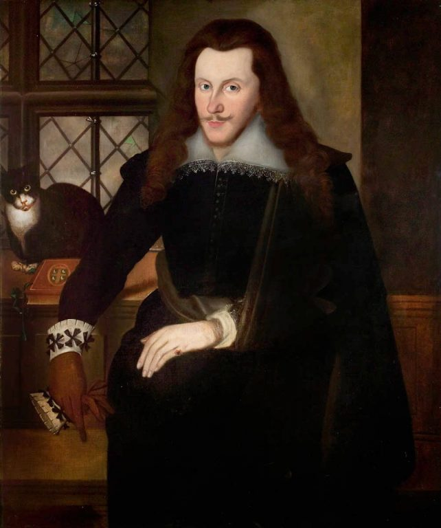 Lord Henry Wriotheseley a long haired thin faced man dressed in Elizabethan noble clothes sits in a room. There are a cat and a book to his elbow, and a single pain of glass is broken in the window.