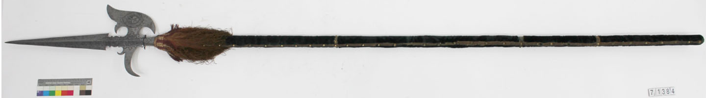 A laid out halberd, with its wooden shaft decorated with horse hair tassel.