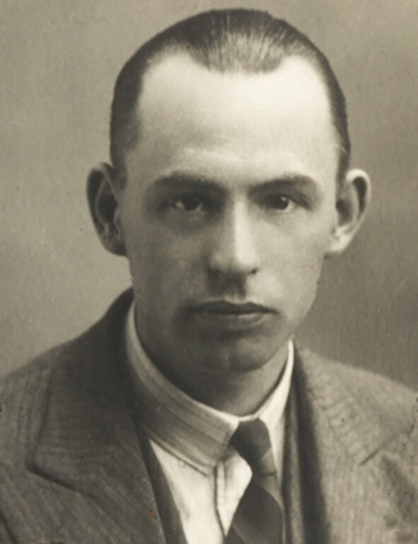 A man poses for a passport photo with slick back hair and a shirt and tie.