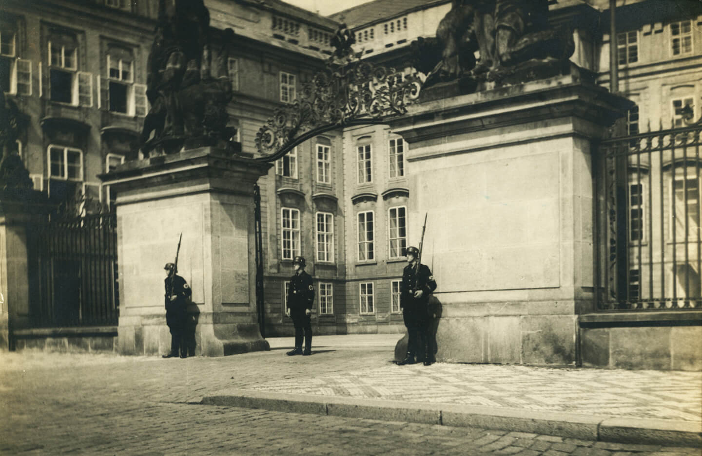 Three Guards with rifles guard a large building's front gate.