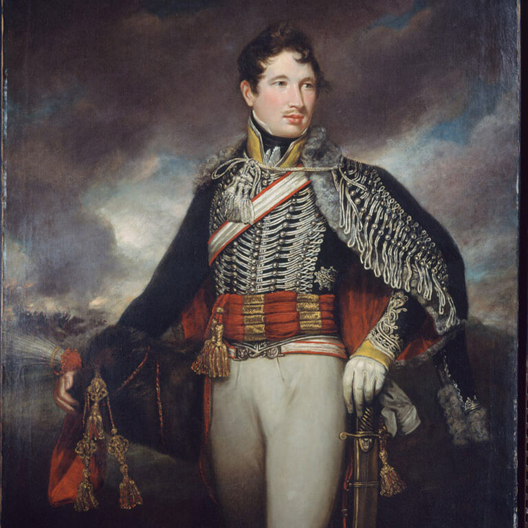A man poses in an ornate black uniform with extensive white trim, a red waste sash, a tall fur helmet and sword.