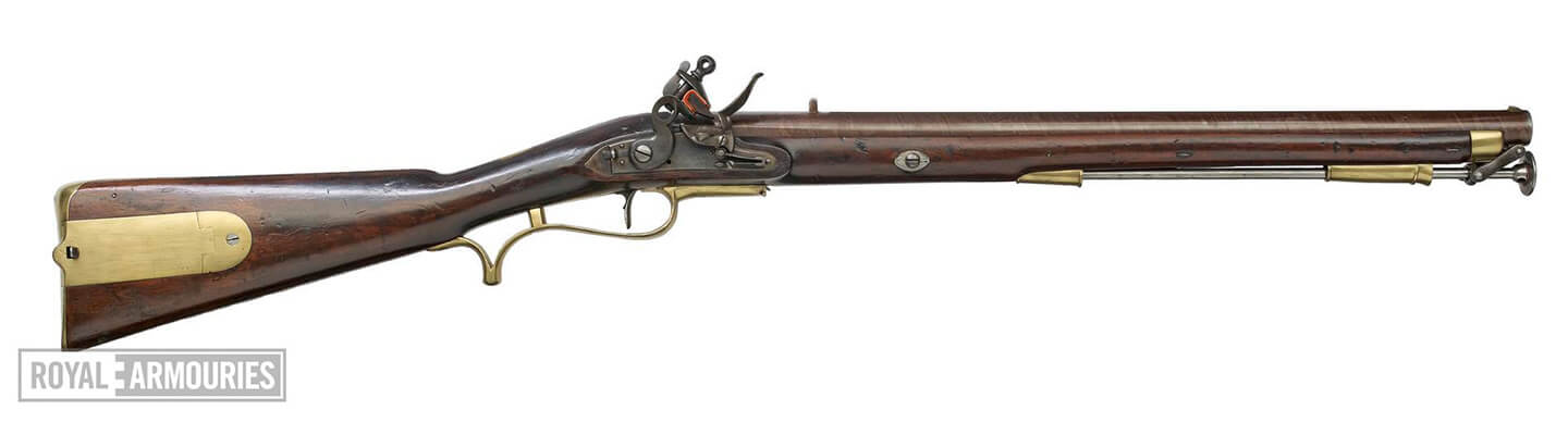 A Baker Rifle on a white background. The body of the gun is made of dark red wood and the metal is polished brass.