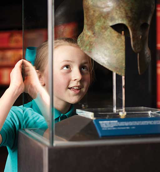 schoolgirl peers excitedly at an ancient Greek helmet