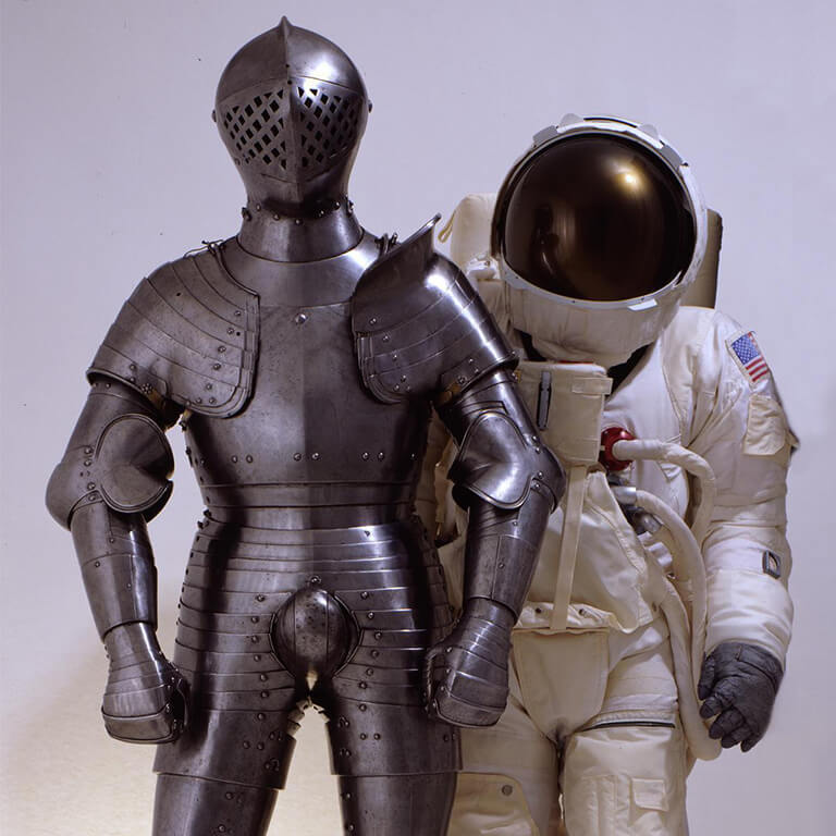 A suit of armour and spacesuit standing side by side