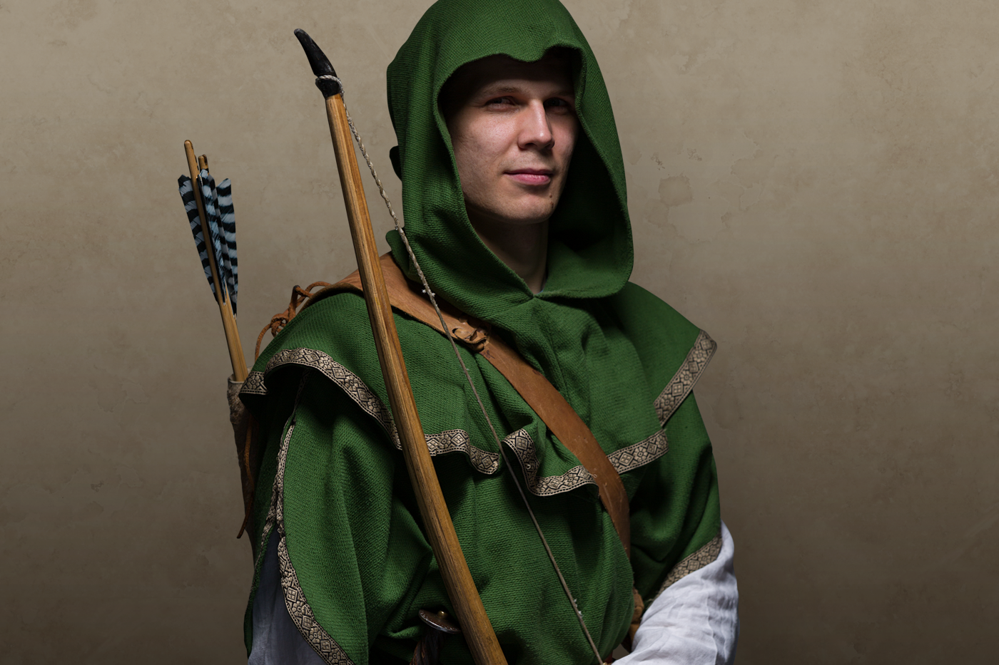 A man in a green medieval hood with a long bow and arrows