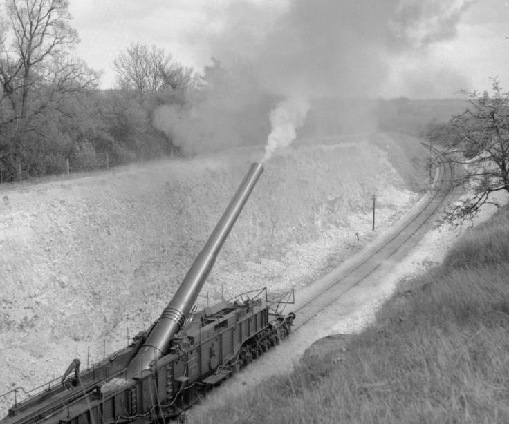Large artillery gun firing from a railway carriage and track in 1941
