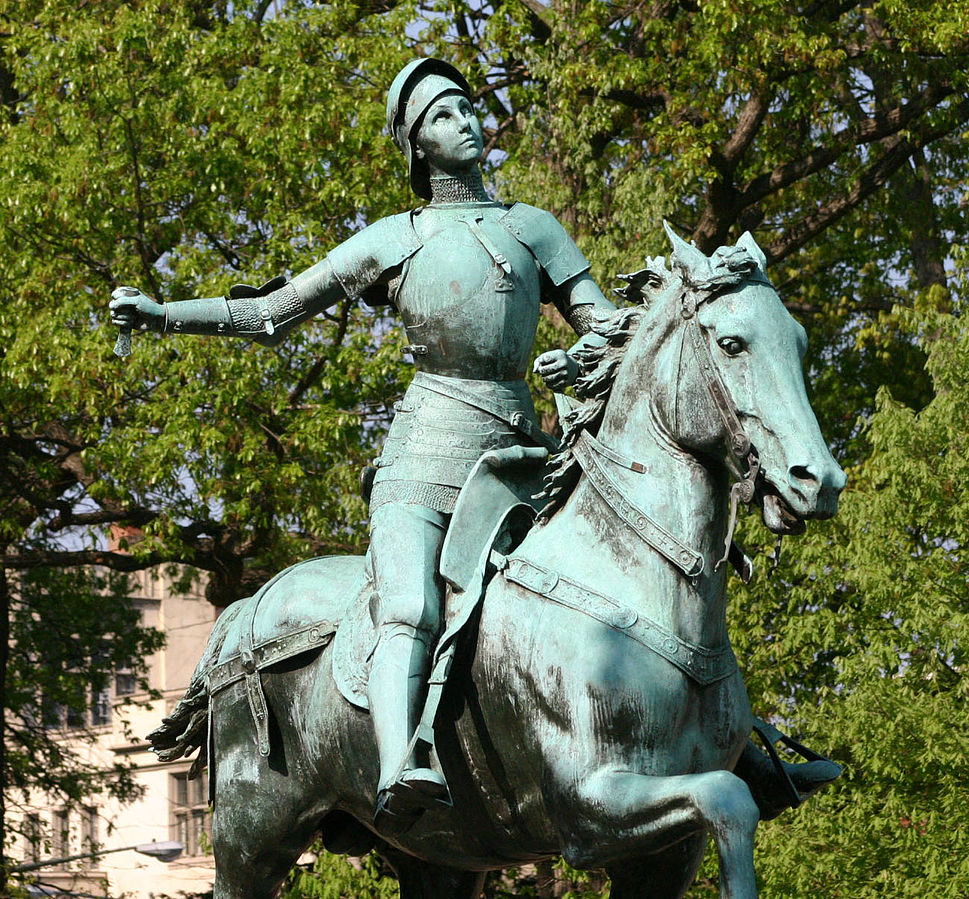 Statue of Joan of Arc riding a horse. She is in full armour and holding a sword