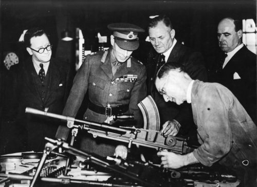 3 men in suits and the King in uniform examine a BREN gun with a technician
