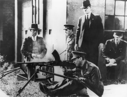 The King in uniform firng a BREN gin while 4 other men look on