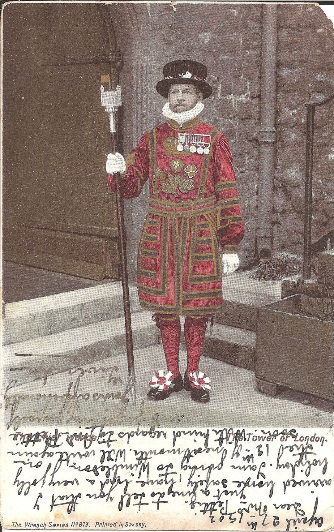 A postcard with a Uniformed Beefeater standing to attention in front of some stairs. There is a hand written message at the bottom of the card.