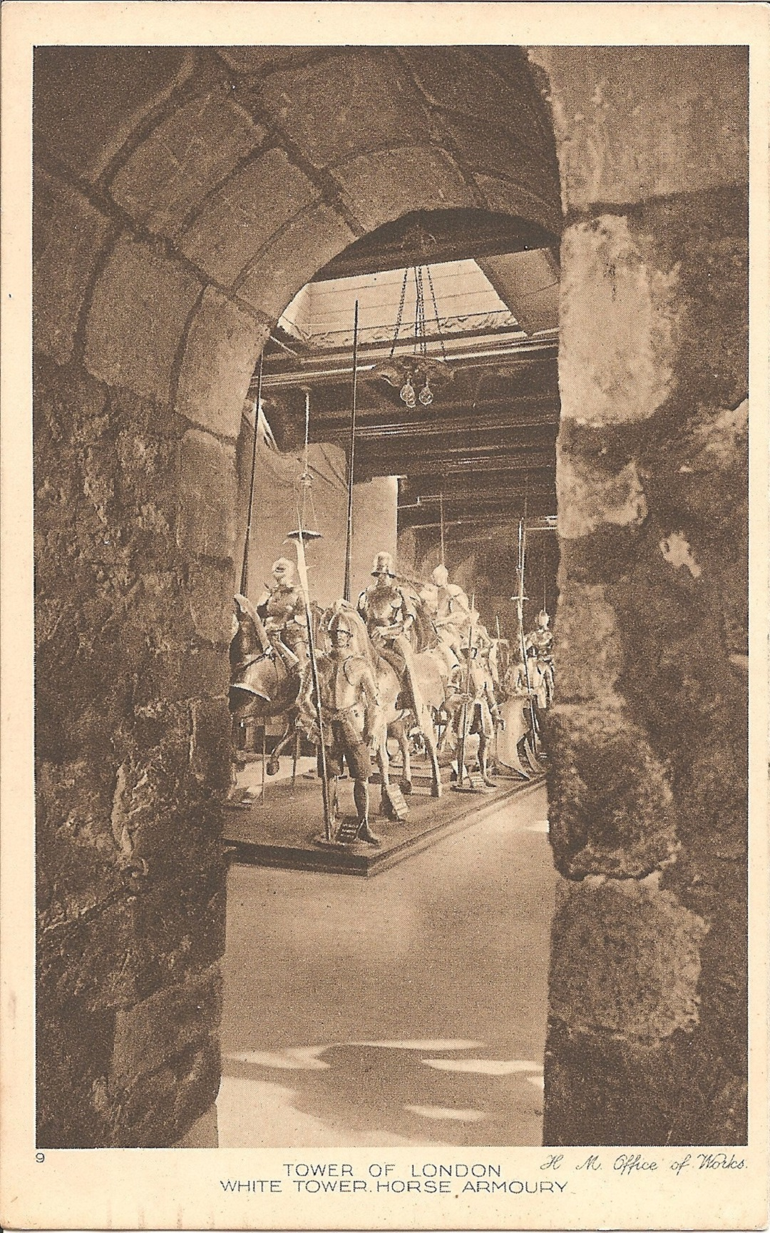 A sphotograph through a stone arch showing a dispaly of armour in sepia on a postcard.