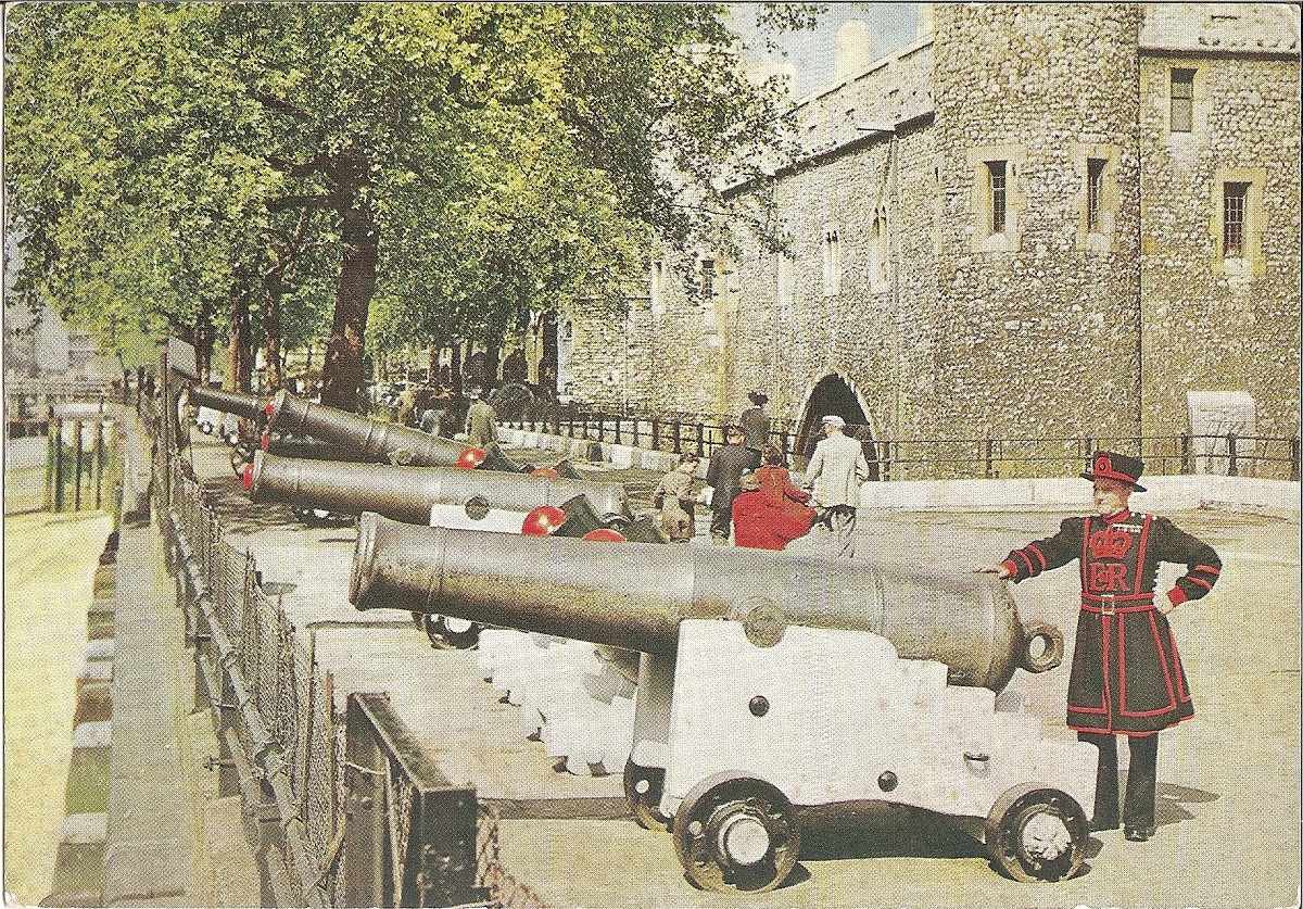 A row of Cannons with tourists and a Yeoman warder behind them