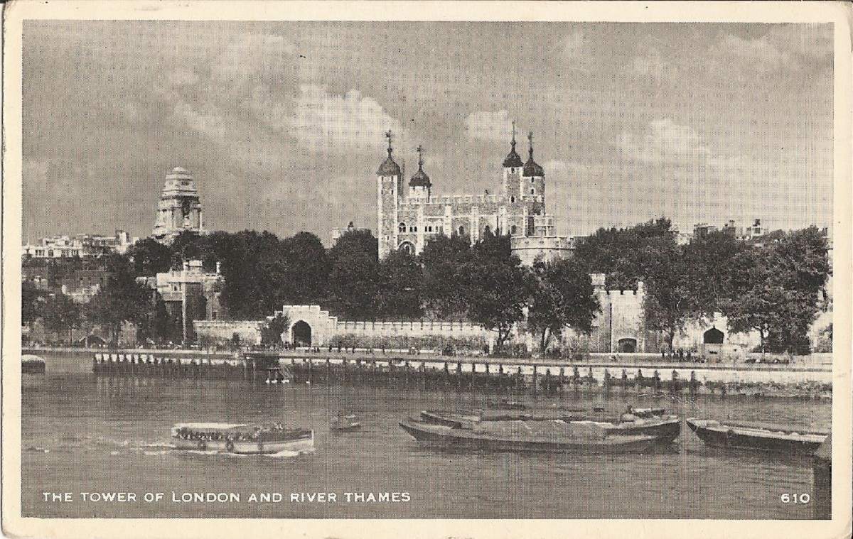 A view of the white tower surrounded by trees from accross the river